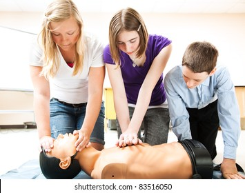 Students practicing CPR life saving techniques on a mannequin.