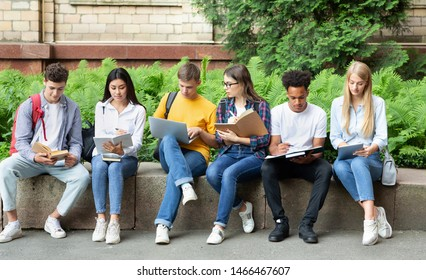 Students preparing for lecture. Teens sitting in university campus with books and devices