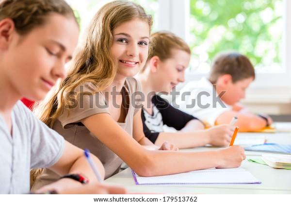 Studenten of leerlingen van de schoolklas die een examentest schrijven in de klas en zich concentreren op hun werk