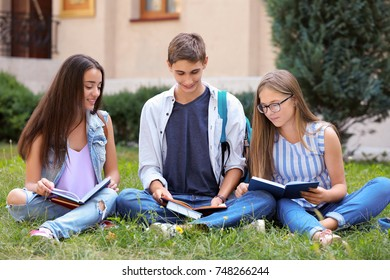 Students reading books outdoors