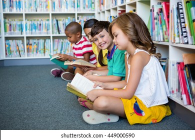 Students reading books while sitting at library in school