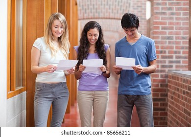 Students reading a piece of paper in a corridor