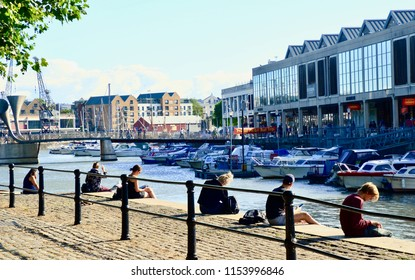 Students relaxing in the evening sun at the waterside harbour at Princes street in Bristol docks. Bristol, in the county of Gloucestershire, England UK. August 2018