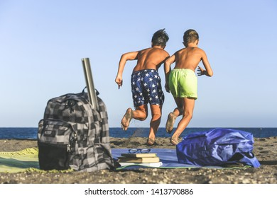 Students runs happy on the beach after the end of school  Two boys running to the ocean to taking bath Concept of freedom and happiness Schoolmates enjoying holidays and summer vacation in a sunny day