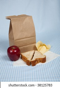 A students sack lunch with a peanut butter and jelly sandwich, potato chips and an apple