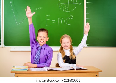 Students sit at their desk during a lesson and raise their hands to answer. Education.
