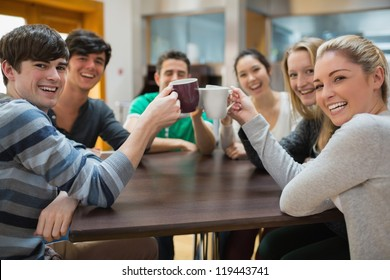 Students sitting clinking cups while smiling in college cafe