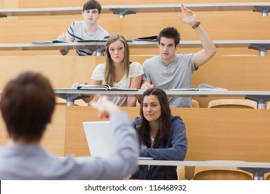 Students sitting at the lecture hall with man raising hand to ask question and lecturer is pointing at him