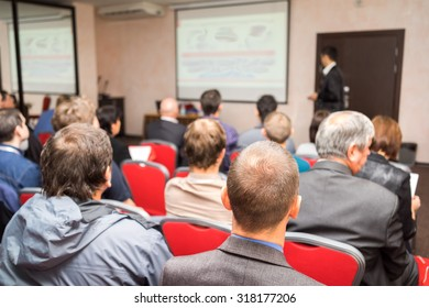 students sitting in a lecture room with teacher in front of the class with white projector slide screen