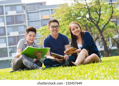 Students sitting on campus lawn and smiling