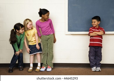 Students standing in classroom. A boy is separate from the girls. Horizontally framed shot.