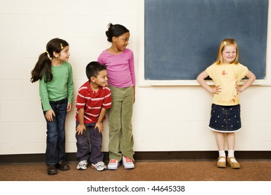 Students standing in classroom. A girl is separate from the group. Horizontally framed shot.