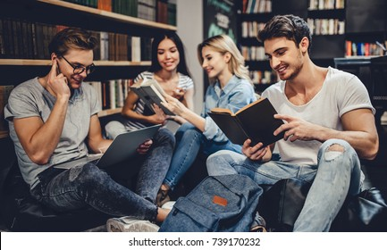 Students are studying in library. Young people are spending time together. Sitting with books and laptop in library.
