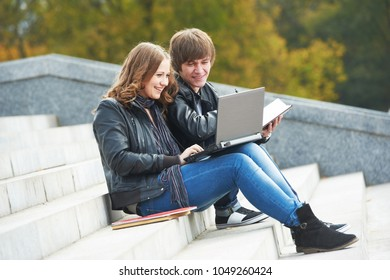 students studying online with laptop computer outdoors