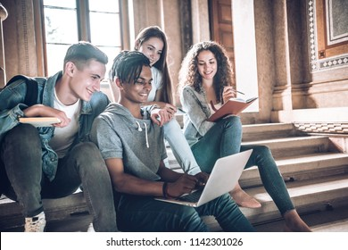 Students are studying together.Multiethnic group of young people looking at a laptop and and sitting on steps in university hall.