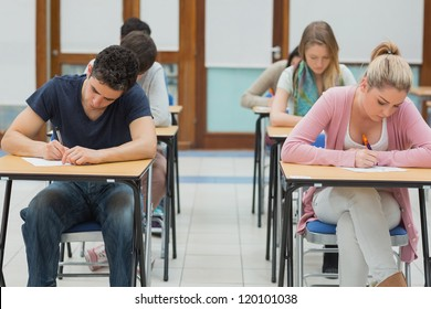 Students taking exams in exam hall in college