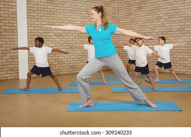 Students and teacher doing yoga pose at elementary school