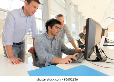 Students with teacher in front of desktop computer