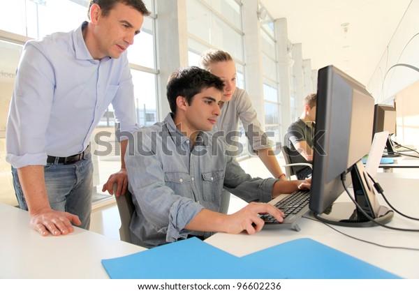 Schüler mit Lehrer vor dem Desktop-Computer