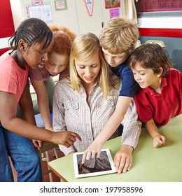 Students and teacher using tablet computer in class in elementary school