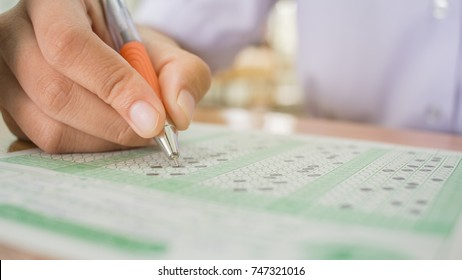 Students testing exams or doing examination with orange pen drawing selected choice on answer sheets in school exams, Education system tests concept.