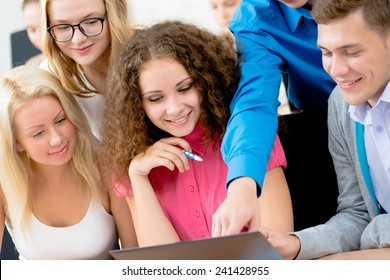 students together to discuss the lecture, come together, looking at laptop monitor