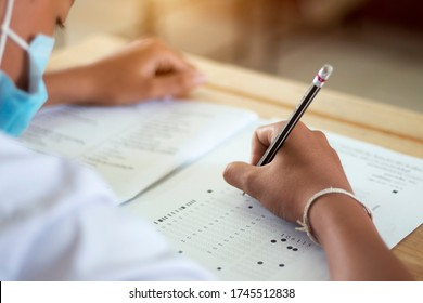 Students in uniform are doing the test in the classroom. Close up hand holding a pencil to write the answer to the exam on wooden table. Evaluation of learning for educational development