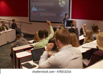 Students at university lecture raise hands to ask questions