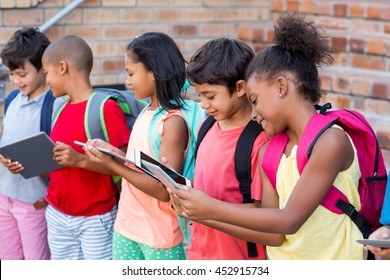 Students using digital tablets outside school