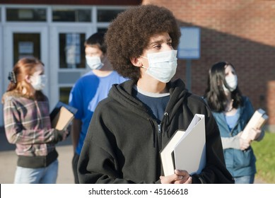 Students of various ethnic backgrounds wearing masks in front of a school