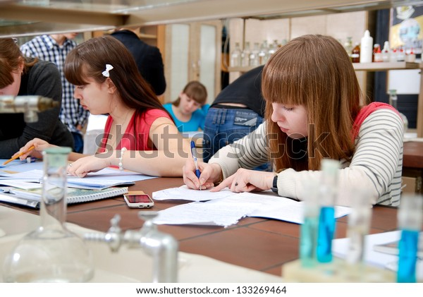 Students at work in the laboratory of chemistry take notes in a notebook