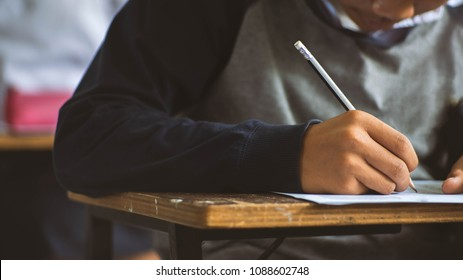 Students writing pen in hand doing exams answer sheets exercises in classroom with stress.16:9 style