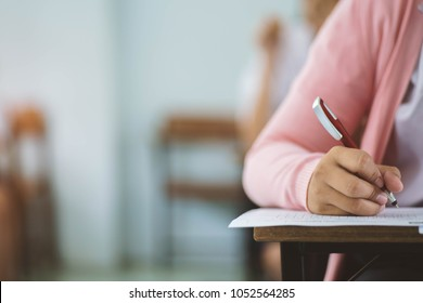Students writing and reading exam answer sheets exercises in classroom of school with stress.