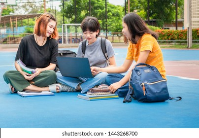 Students young asian together reading book study smiling with tablet,laptop computer at university high school campus.