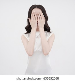 Studio art fashion photo of woman closing her face with her hands on white background. Health and beauty