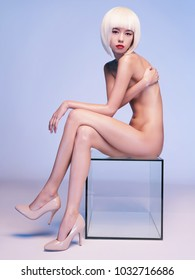 Studio art photo of elegant nude woman sitting on glass cube on white background. Perfect body. Beauty and cosmetology