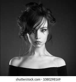 Studio art portrait of beautiful woman with elegant hairstyle on black background