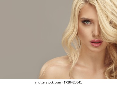 Studio beauty picture of european woman with healthy blonde long wavy hair on isolated background