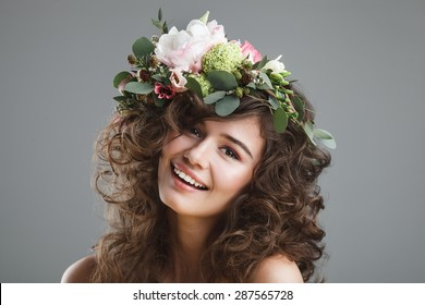 Studio beauty portrait of cute young girl with flower crown