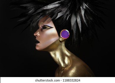 Studio beauty portrait of young woman with black graphic makeup, gold body and fashion haistyle