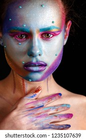 Studio beauty portrait of young woman with color graphic creative professional makeup