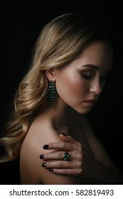 Studio beauty portrait of young woman wearing green ring and earrings on black background.