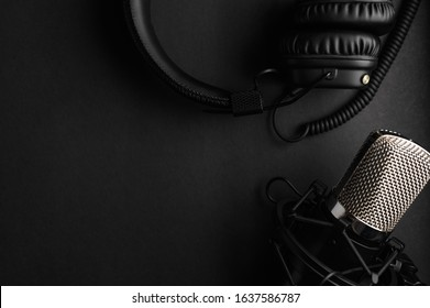 Studio black studio microphone with studio headphones on a black background. Banner. Radio, work with sound, podcasts.