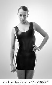 Studio black and white image of young woman wearing latex
