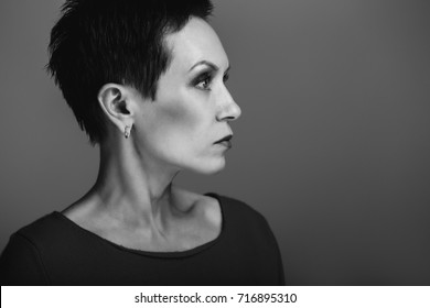 Studio black and white portrait of beautiful cool edgy middle aged white caucasian brunette woman. Aged European model with dark short hair looking away.