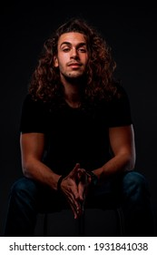 Studio body shot of a fashion male model with curly long hair wearing stylish clothes