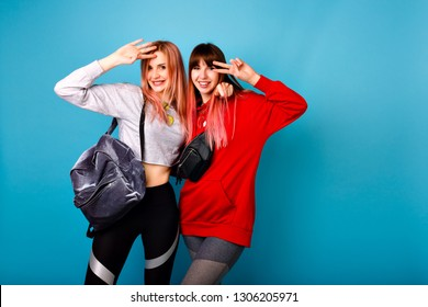 Studio bright portrait of two happy hipster woman having fun together, fitness sportive couple of best friend wearing bright trendy hoodies and legging , say hello and showing peace gesture, students.