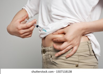 Studio close up of blonde caucasian woman holding needle making self injection in abdomen, health care, medicine treatment, vaccination, hormonal therapy, in vitro fertilization, isolated background