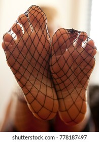 Studio Close Up Detailed Shot Of Sexy Beautiful Female Feet In Black Fishnet Stockings With Toes