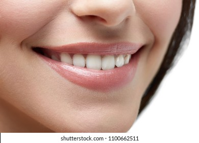 Studio close up of model's beatiful smile on white background. Healthy smooth skin, white teeth, plump rosy lips, little nose and dark brown hair on background. Beatiful smile.